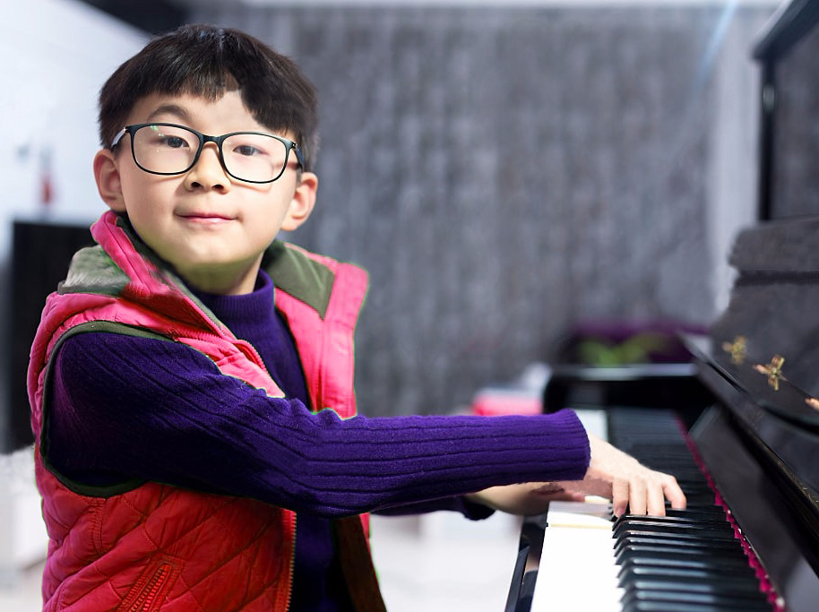 Boy happily plays the piano